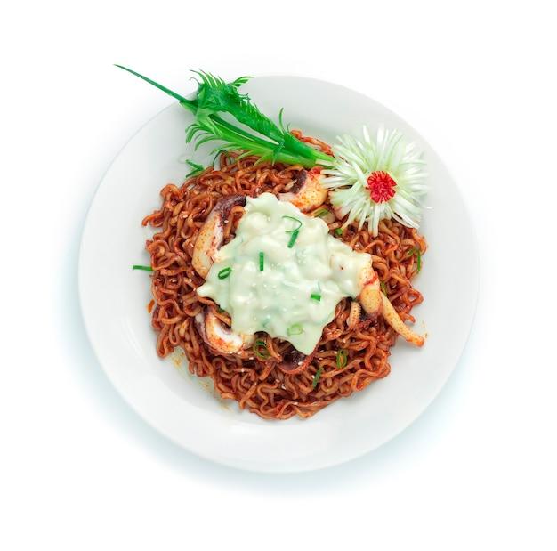 Nouilles épicées coréennes sautées avec des calamars dans une sauce épicée sur le fromage mozzarella style de cuisine coréenne décorez la forme de fleur d'oignon de printemps de poireau sculpté