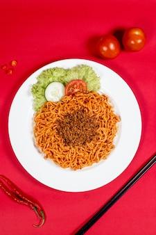 Nouilles épicées avec garniture et légumes sur fond rouge