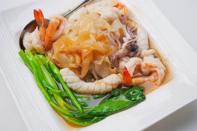 Nouilles frites aux fruits de mer et kale en sauce