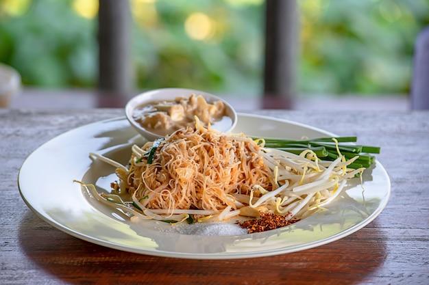 Nouilles frites avec des oignons nouveaux et des germes de soja sur une plaque blanche avec garniture.
