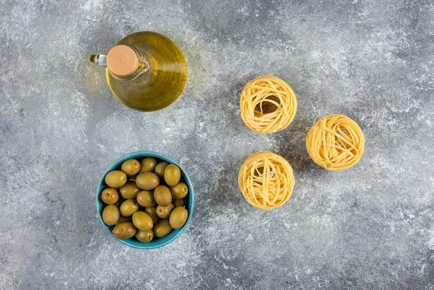 Nouilles, huile et olives vertes sur pierre.