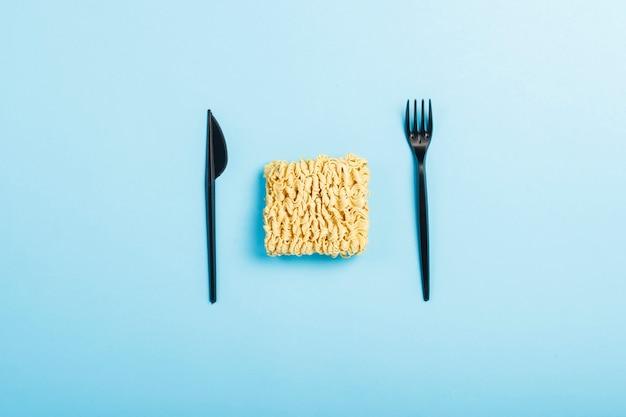 Nouilles instantanées asiatiques et plats jetables en plastique sur une surface bleue. le concept de plats cuisinés, restauration rapide, malbouffe. mise à plat, vue de dessus.