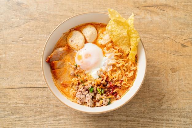 Nouilles instantanées au porc et boulettes de viande dans une soupe épicée ou nouilles tom yum à l'asiatique