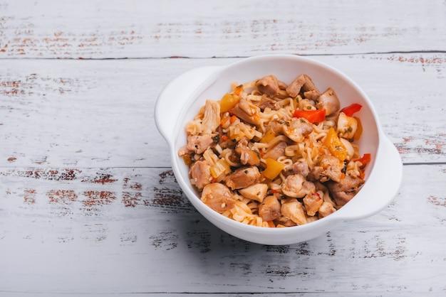 Nouilles instantanées au poulet et au poivre avec sauce épicée dans un bol blanc