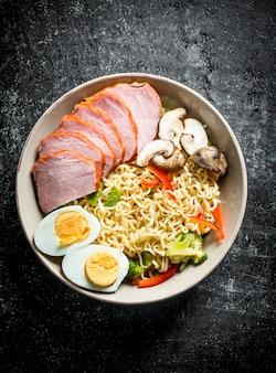 Nouilles instantanées aux légumes, jambon et oeuf sur table rustique