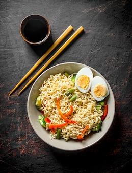 Nouilles instantanées aux œufs, légumes et sauce soja. sur rustique foncé