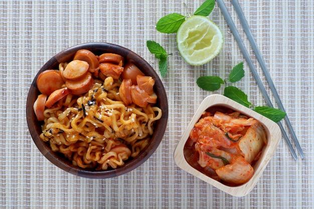 Nouilles instantanées coréennes, épicé, saucisse, kimchi dans un bol en bois avec baguette sur bambou