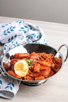 Nouilles instantanées coréennes et tteokbokki dans une sauce rouge épicée coréenne, rabokki (ramen topokki), style coréen populaire de cuisine de rue