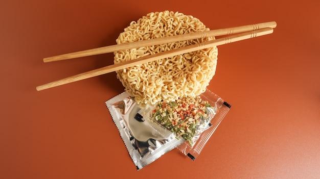 Nouilles instantanées crues avec des baguettes et des épices. copiez l'espace cuisine asiatique. pâtes, pour la préparation desquelles il suffit de verser de l'eau bouillante et d'attendre quelques minutes. spaghettis parfumés.