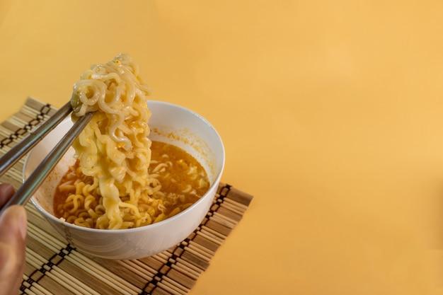 Les nouilles instantanées cuites avec des baguettes peuvent être consommées comme plat principal ou comme apéritif d'abord.
