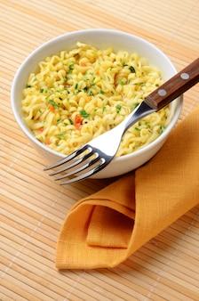 Nouilles instantanées cuites dans un bol avec une fourchette