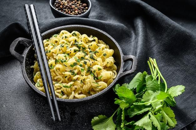 Nouilles instantanées cuites avec de la viande de soja dans une casserole. plat végétarien. fond noir. vue de dessus