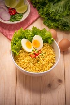 Nouilles instantanées dans un bol avec des légumes et des œufs durs sur fond de bois