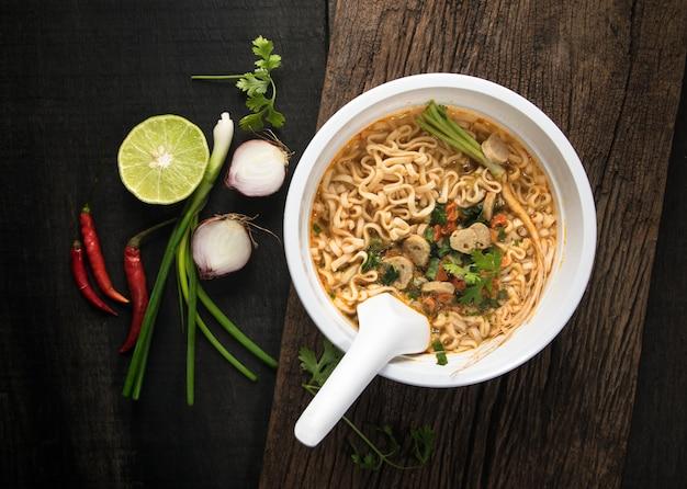 Nouilles instantanées dans un bol en plastique et plats d'accompagnement de légumes sur fond de bois.