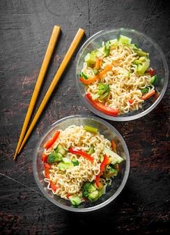Nouilles instantanées dans des bols en verre avec des légumes sur table rustique