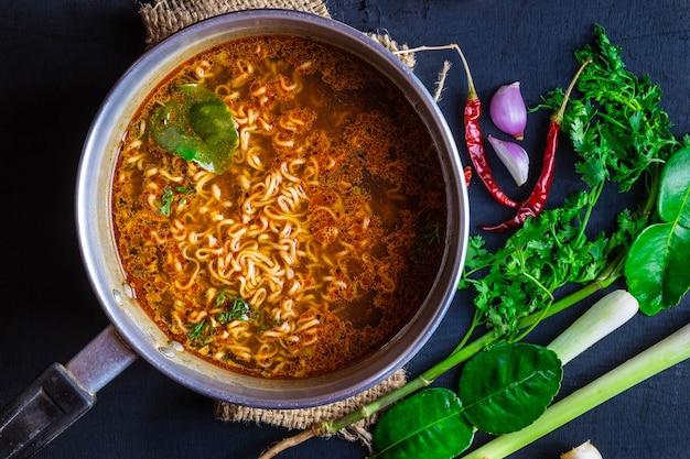 Nouilles instantanées dans un pot épicé avec des épices et des légumes.