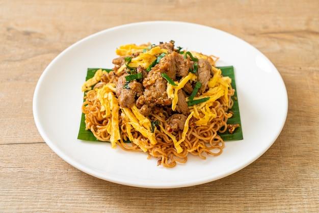 Nouilles instantanées sautées au porc et aux œufs - style de cuisine de rue locale asiatique