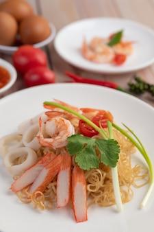 Nouilles instantanées sautées aux crevettes et au crabe dans un plat blanc.