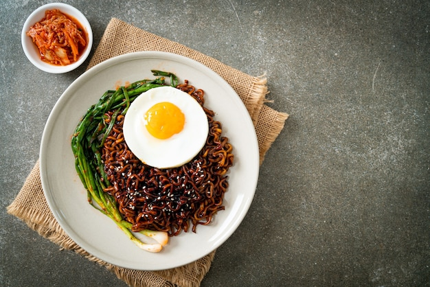 Nouilles instantanées séchées faites maison à la sauce noire épicée coréenne avec œuf au plat et kimchi