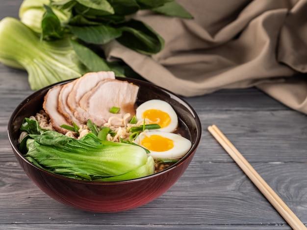 Nouilles instantanées avec tranches de porc et bok choy.