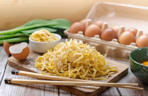 Nouilles jaunes aux œufs recouvertes de farine sur une planche à découper et des baguettes autour des œufs, des coquilles d'œufs, du jaune d'œuf et du chou chinois sur une table en bois