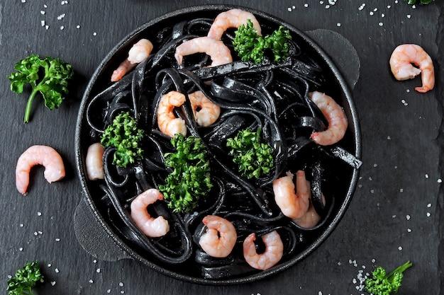 Nouilles noires aux crevettes et épices. tendance alimentaire. déjeuner végétarien. pâtes à l'encre de seiche.