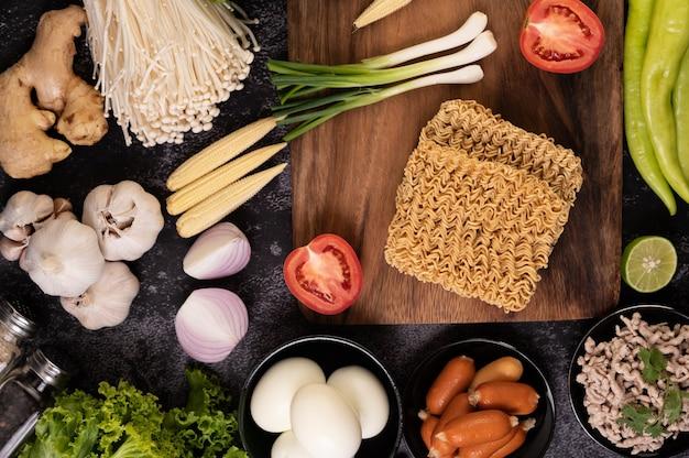 Nouilles sur une planche à découper en bois avec tomate, citron vert, oignon nouveau, piment et maïs miniature