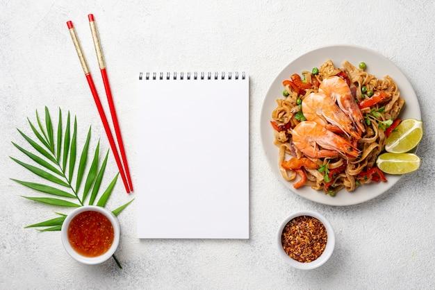 Nouilles plat poser avec des baguettes de crevettes et des légumes et des épices avec cahier vierge