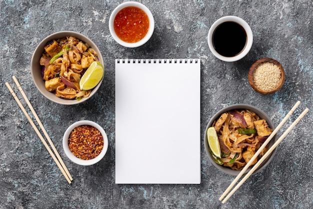 Des nouilles plates dans des bols et des sauces avec un cahier vierge