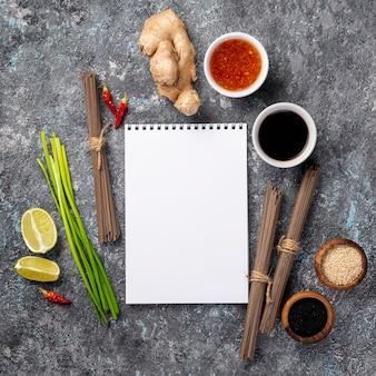 Des nouilles plates et des épices avec un cahier vierge