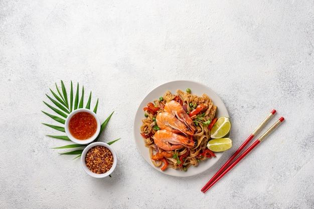 Nouilles plates avec légumes et crevettes avec des baguettes et des épices