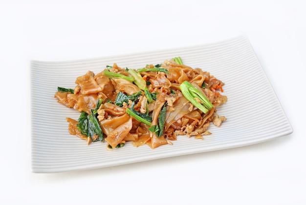Nouilles et porcs plats sautés avec sauce de soja noire dans une assiette carrée