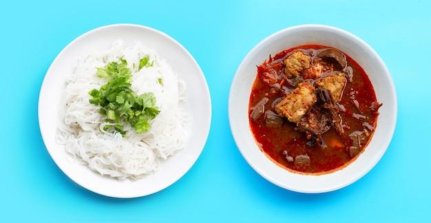 Nouilles de riz au curry de porc du nord de la thaïlande sur fond bleu.