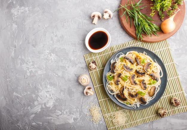 Nouilles de riz aux champignons champignons sur un béton gris. vue de dessus.