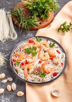 Nouilles de riz aux crevettes ou crevettes et petites pieuvres sur plaque en céramique grise sur fond de béton noir