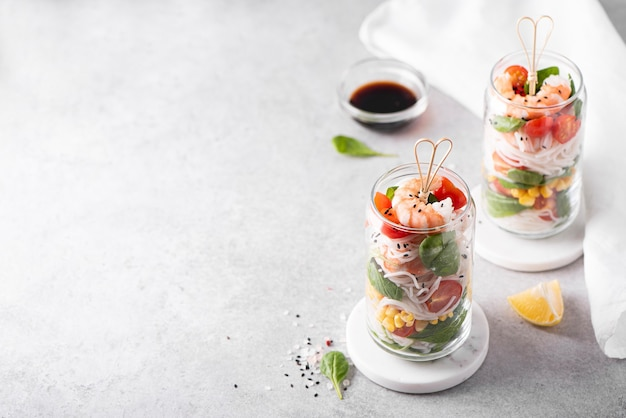 Nouilles de riz aux crevettes et légumes dans un bocal en verre sur un tableau blanc, vue du dessus
