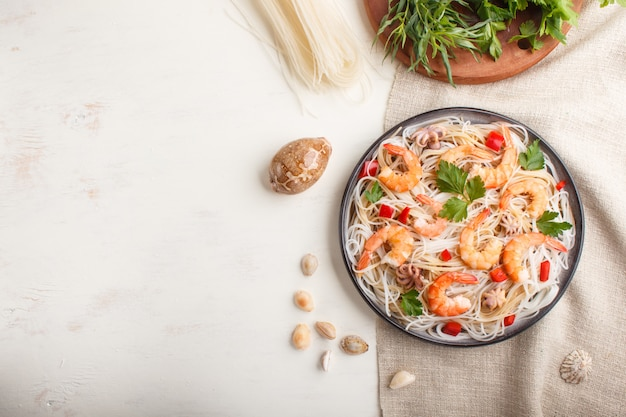 Nouilles de riz avec des crevettes ou des crevettes et de petites pieuvres sur une plaque en céramique grise sur un bois blanc. vue de dessus.