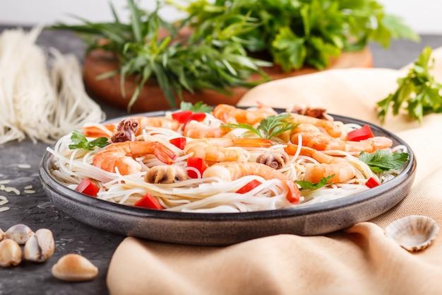 Nouilles de riz avec des crevettes ou des gambas et de petites pieuvres sur une plaque en céramique grise sur un fond de béton noir