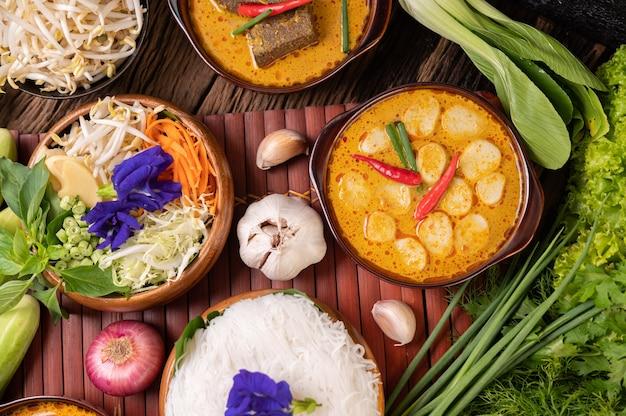 Nouilles de riz dans un bol de pâte de curry avec piment, concombre, haricot long, citron vert, ail et oignon nouveau
