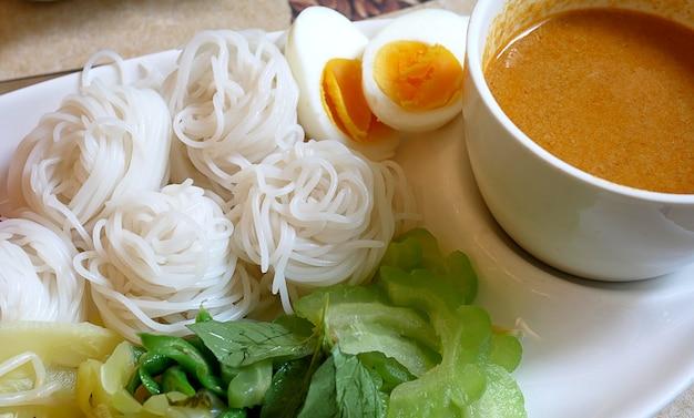 Nouilles de riz dans une sauce au poisson au curry avec des légumes. délicieux repas thaïlandais servi avec un œuf à la coque.