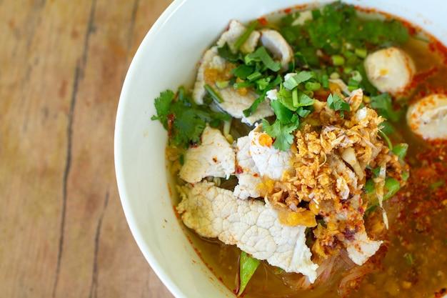 Nouilles de riz dans une soupe épicée avec une boule de porc, des légumes et du porc sur un bureau en bois à la cantine