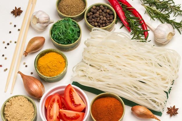 Nouilles de riz et épices sèches dans de petits bols verts. oignons, brins de romarin et bâtonnets de bambou. vue de dessus.