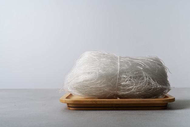 Nouilles de riz fines crues sur un plat en bambou avec des baguettes sur la surface de la pierre avec espace de copie.