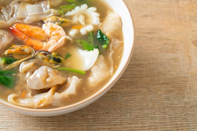 Nouilles de riz larges aux fruits de mer dans une sauce à la sauce - style de cuisine asiatique