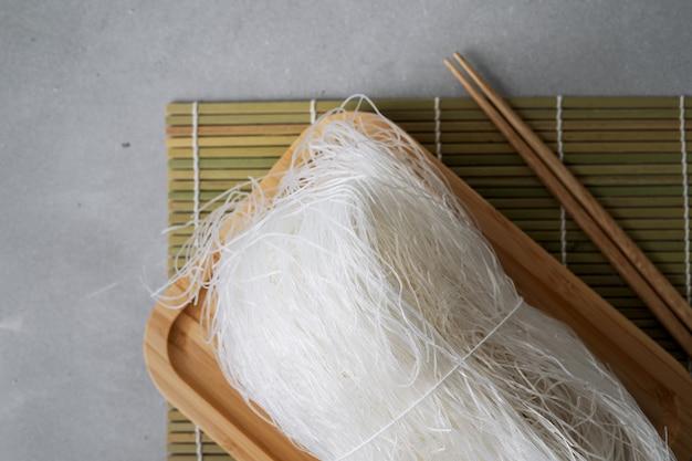 Nouilles de riz minces crues sur plat en bambou sur la surface de la pierre avec des bâtons