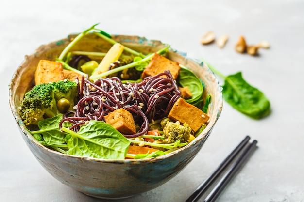 Nouilles de riz noir végétalien au tofu et légumes, fond blanc.