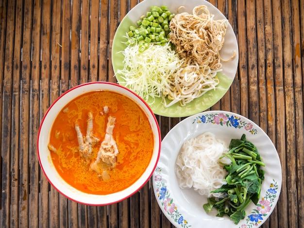 Nouilles de riz servies avec des pattes de poulet dans une sauce au curry de poisson. plat d'accompagnement avec des légumes.