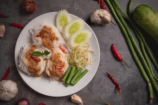 Nouilles de riz thaï dans une sauce au curry de poisson sur une table en bois.