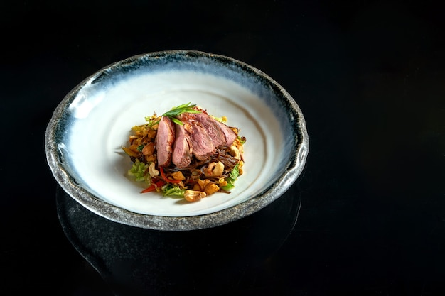 Nouilles de sarrasin aigre-douce au canard, cacahuètes, légumes et oignons, servies dans un bol blanc