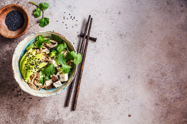 Nouilles de sarrasin - soba avec tofu, brocoli, avocat, semis et coriandre, vue de dessus, espace copie. concept de nourriture végétalienne saine.